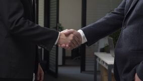 Two successful businessmen in suits are shaking hands in the office in the background, an African businessman, a. Caucasian businessman. 60 fps 4k stock footage