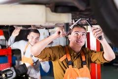 Two successful car mechanics. Portrait of two positive car mechanics at workshop Royalty Free Stock Photos