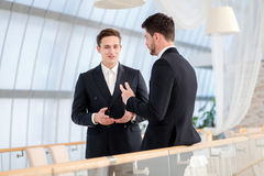 Two successful and confident businessman talking in an office.  Stock Photo