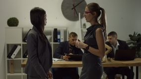 Two businesswomen having informal meeting in office. Two successful female collegues talking and discussing about work in modern office while standing against stock footage