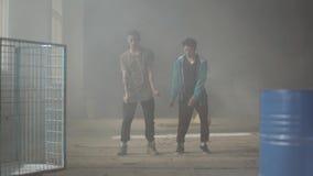 Two successful hip-hop dancers dancing street dances in an abandoned building. Friends practicing in break-dance. Hip. Two successful hip-hop dancers dancing stock footage