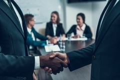 Two successful multi ethnic businessmen make deal with firm handshake. Business Meeting. Encounter in Boardroom Stock Image