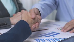 Two successful partners adopt company growth strategy, handshaking at meeting. Stock footage stock video footage
