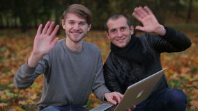 Two successful programmers says hello hi welcome to the camera. Two successful programmers greeting the camera after using laptop computer in the city park stock footage