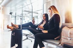 Two successful women resting in arrival hall waiting for a transfer sitting with their legs on suitcase surfing the. Internet using mobile phone at airport Stock Images