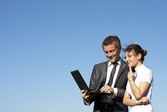 Two successful workers in the street with a laptop Royalty Free Stock Image