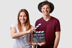 Two successful young female and male famous producers or directors hold film clapper, participate in shooting film, have joyful ex. Pressions, pose against white Royalty Free Stock Photos