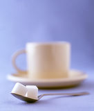 Two sugar cubes with a cup of coffee on a saucer. Coffee cup and saucer with two sugars on a spoon Royalty Free Stock Photography