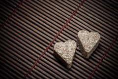 Two sugar hearts on wooden texture Royalty Free Stock Photography