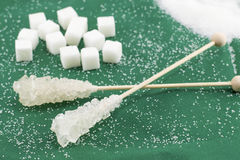 Two sugar sticks and sugar cubes on green Royalty Free Stock Images