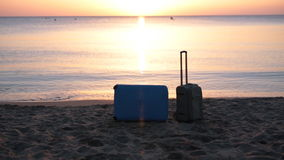 Two suitcases on the beach. Travel suitcase is alone on a beach with the lake or ocean in the background stock video