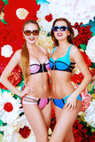 Two summer girls. Two pretty girls in summer swimsuits and sunglasses posing together over bright floral background. Summer fashion Stock Images