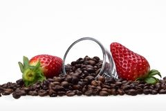 Two summer strawberry berries and a glass cup among coffee grains royalty free stock image