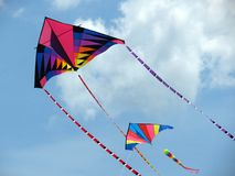 Two Summertime Kites. Two brightly coloured kites soar up to the clouds on a summer's day stock photos