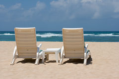 Two sun beach chairs near ocean Royalty Free Stock Photo