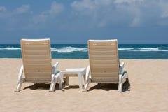 Two sun beach chairs near ocean. Two sun beach chairs on shore near ocean Royalty Free Stock Photo