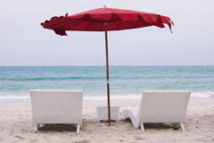 Two sun beds at the beach with red umbrella Royalty Free Stock Photography