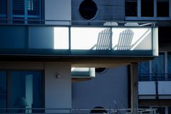 Two sun chairs cast shadows on a balcony at a modern residential Royalty Free Stock Photo