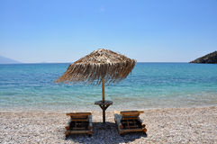 Two sun chairs on empty beach of samos, greece Stock Photos