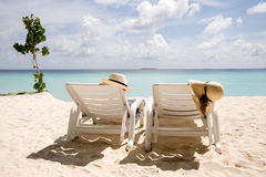 Two sun loungers on the beach Stock Photos