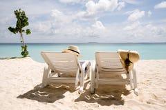 Two sun loungers on the beach Stock Photos