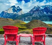 Two sun loungers overlooking the Los Cuernos. Two comfortable red sun loungers overlooking the cliffs of Los Cuernos. Torres del Paine National Park. Summer in stock image