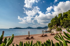 Two sun loungers and parasols. On the sandy beach royalty free stock photo