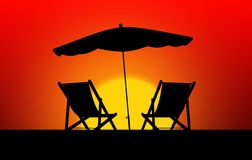 Two sun loungers and parasols at sunset Stock Image