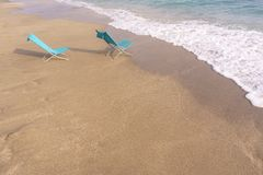Two sun loungers on the sandy beach. Two turquoise chaise Lounges on the sandy beach stock images