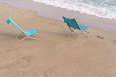 Two sun loungers on the sandy beach. Two turquoise chaise Lounges on the sandy beach royalty free stock photo