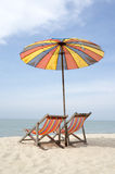 Two sun loungers and an umbrella on a beach Stock Images