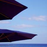 Two sun umbrellas. Two dark blue umbrellas providing shade from the sun Stock Photos