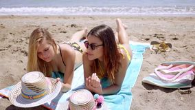 Two sunbathing friends on a beach by the ocean stock video footage