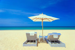 Two sunbed and one umbrella on the beach Royalty Free Stock Photos