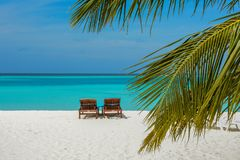 Two sunbeds on the beautiful beach at the tropical island at resort. At Maldives Stock Image