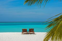 Two sunbeds on the beautiful beach at the tropical island. At Maldives Royalty Free Stock Images