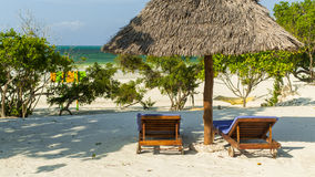 Two sunbeds and parasol on the tropical sandy beach. Vacation an Stock Photo