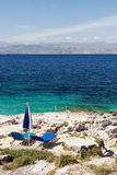 Two sunbeds on the rocky sea shore Royalty Free Stock Images