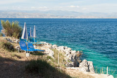 Two sunbeds on the rocky sea shore Stock Photo