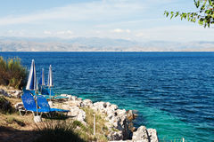 Two sunbeds on the rocky sea shore Stock Images
