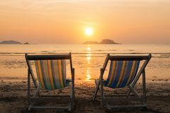 Two sunbeds on the sea beach during sunset. Relax. Stock Photo