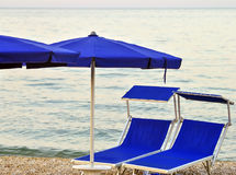Two sunbeds on a stony beach Royalty Free Stock Photography