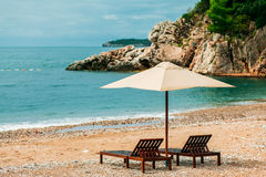 Two sunbeds  and umbrella at luxury beach resort Stock Photos