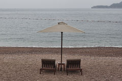 Two sunbeds and umbrella with small table Royalty Free Stock Photos