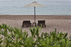 Two sunbeds and umbrella with small table Royalty Free Stock Photo