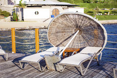 Two sunbeds and umbrella on a wooden pier near the sea Stock Photos