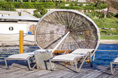 Two sunbeds and umbrella on a wooden pier near the sea Royalty Free Stock Photo
