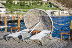 Two sunbeds and umbrella on a wooden pier near the sea Royalty Free Stock Photography