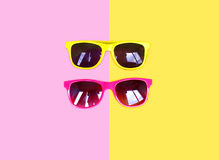 Two sunglasses yellow pink over colorful background Royalty Free Stock Photo