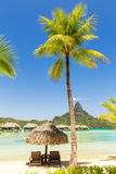 Two sunlounger chairs under a thatched parasol on a sand beach w. Ith a view on the lagoon and Mount Otemanu on the tropical island of Bora Bora, near Tahiti, in Stock Images
